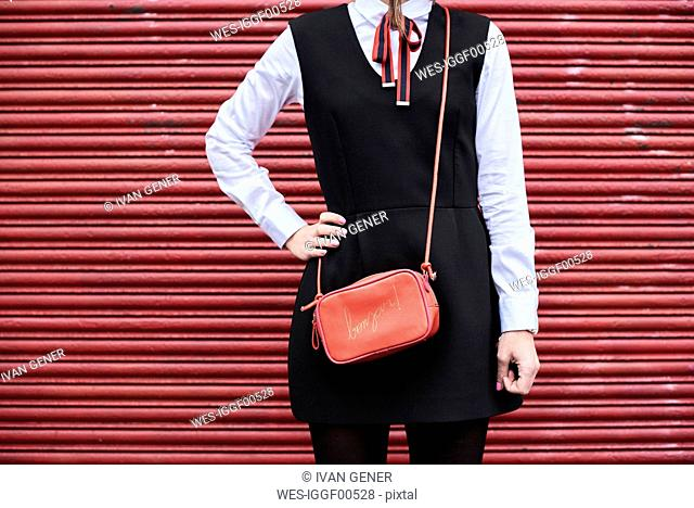 Fashionable woman with red handbag wearing black dress standing in front of red roller shutter
