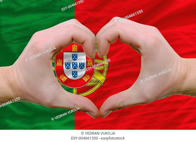 Heart and love gesture showed by hands over flag of portugal bac