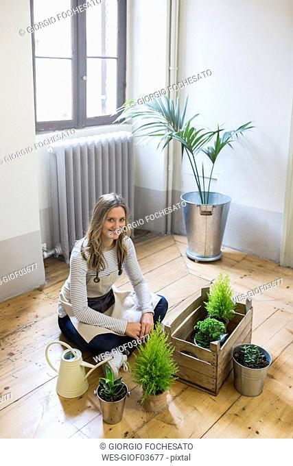 Portrait of smiling woman sitting on floor at home caring for plants