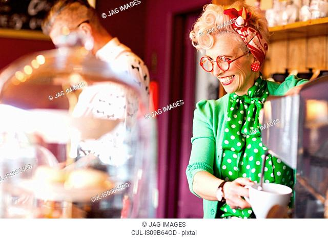Quirky vintage woman using coffee machine in tea room