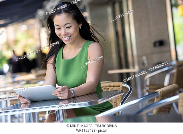 A woman sitting outdoors at a cafe table using a digital tablet