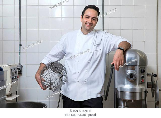 Portrait of chef in commercial kitchen holding whisk, looking at camera smiling