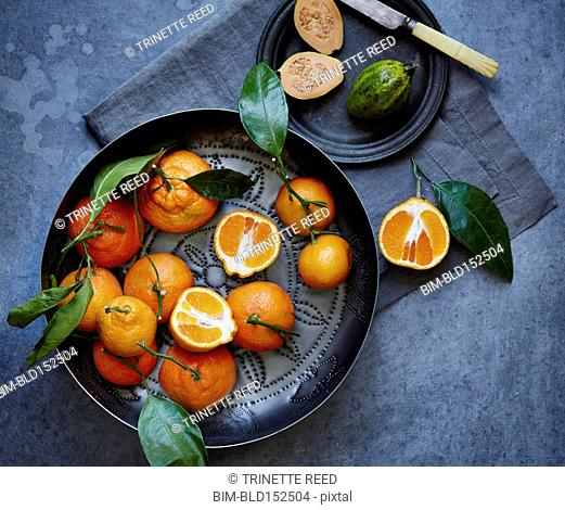 High angle view of oranges, pot and plate