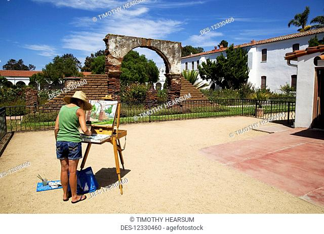 Woman Painting The Scene On An Easel In A Courtyard At Mission San Luis Rey, Near Oceanside, Ca In Late Summer; California, United States Of America