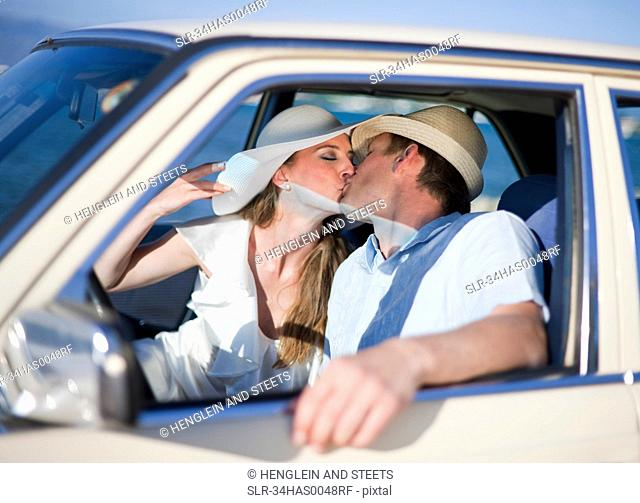 Newlywed couple kissing in car