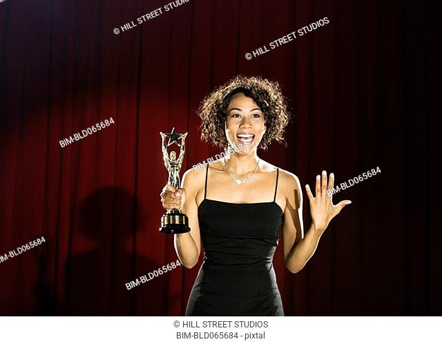 Mixed race woman standing on stage with trophy