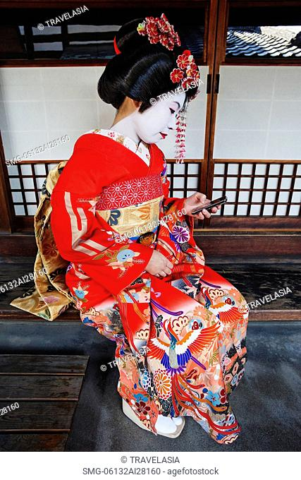 Geisha in red Kimono looking at mobile phone