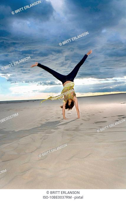 Woman does cartwheel at beach