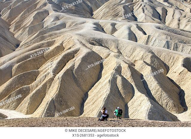 A pair of photographers are tiny on a hillside at Zabriskie Point in Death Valley compared to the massive scale of the iconic sandstone landscape in front of...
