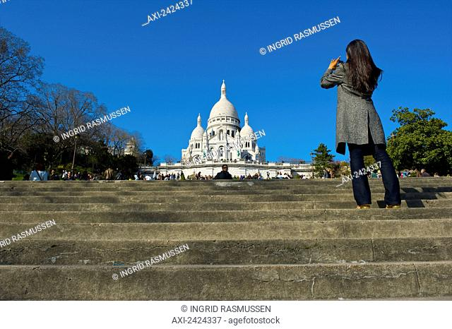Tourist stands on the steps and takes a photograph of the Basilica of the Sacred Heart of Paris; Paris, France