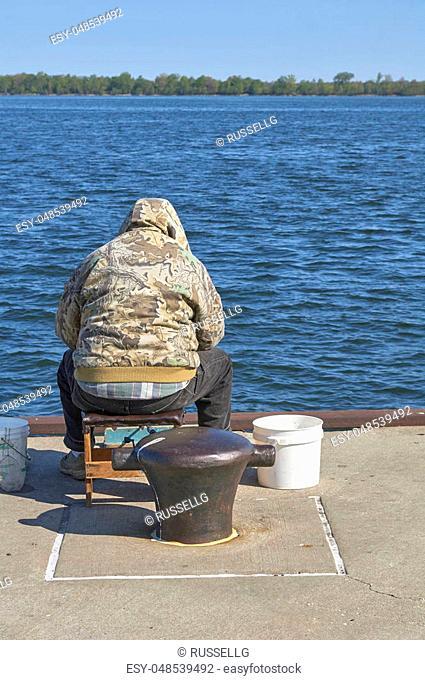 Finger Lakes, New York. Man on dock fishing
