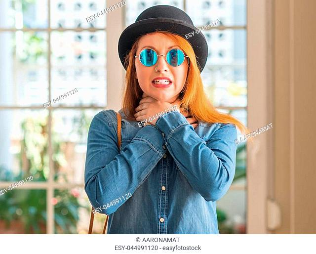 Stylish redhead woman wearing bowler hat and sunglasses shouting and suffocate because painful strangle. Health problem. Asphyxiate and suicide concept