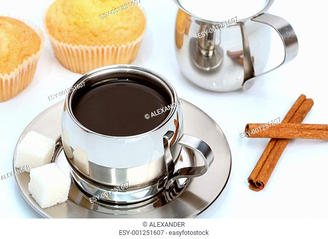 Cup of black coffee with muffin, milk and cinnamon