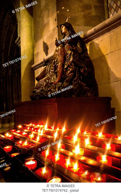 Candles in front of Virgin Mary statue in Monastery of Jeronimos