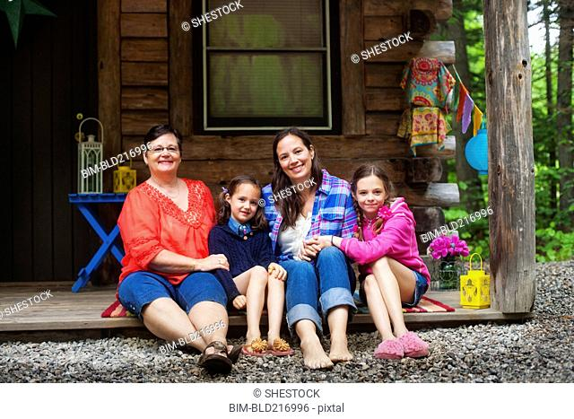 Three generations of Caucasian women smiling on cabin porch