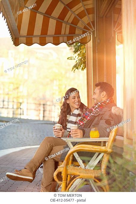 Young couple drinking milkshakes at sidewalk cafe