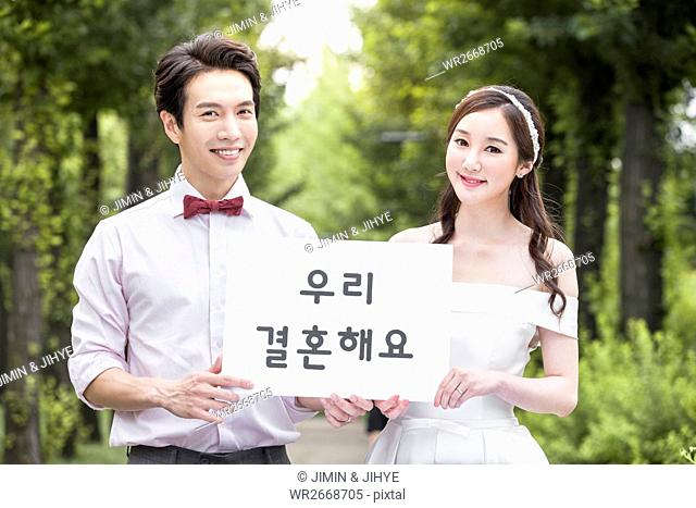 Young smiling wedding couple with Korean message outdoors