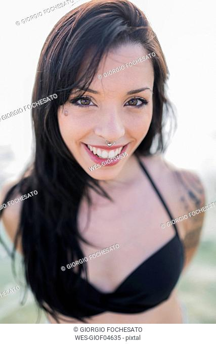 Portrait of smiling young woman with nose piercing at the sea
