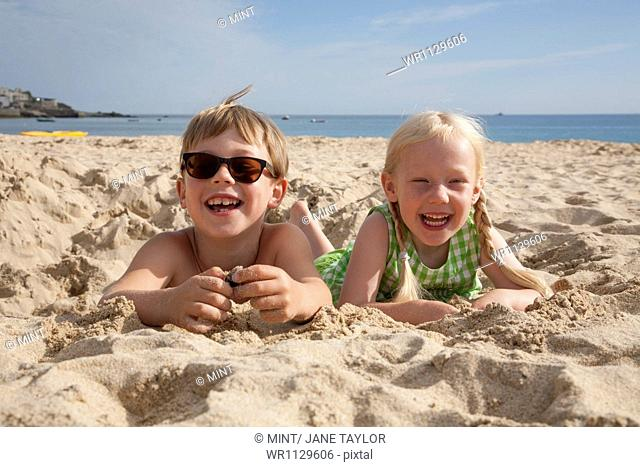 A boy and girl lying on their stomachs on the sand, laughing and looking at the camera