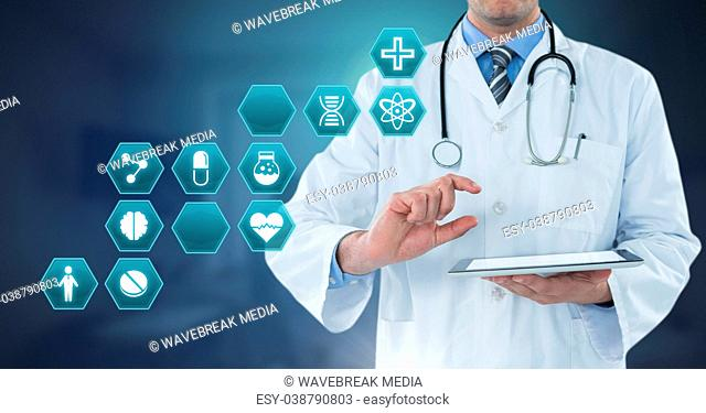 Male doctor holding tablet with medical interface hexagon icons