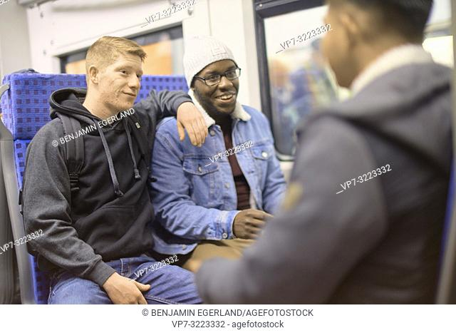 young men sitting in public transport, in Munich, Germany