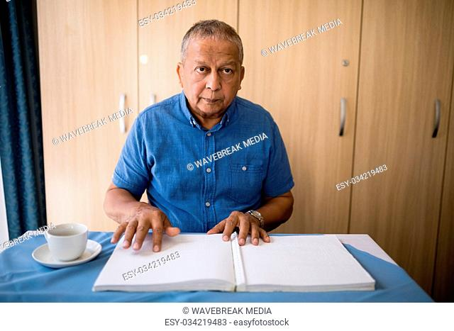 Senior man sitting with book and coffee cup at table