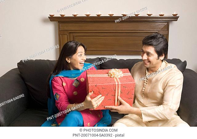 Close-up of a couple holding a diwali gift and smiling
