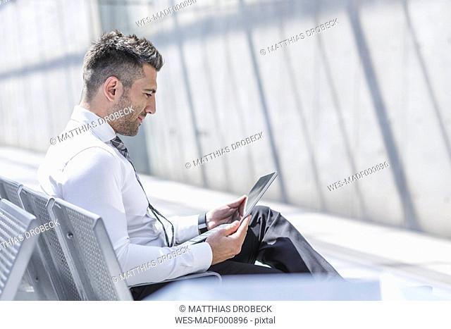 Businessman using digital tablet at waiting area