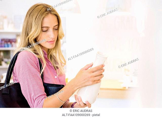 Woman looking at vase in store