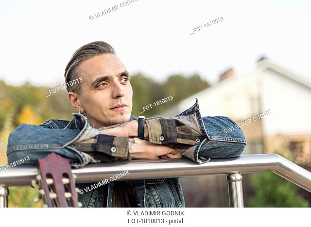 Serene man leaning on railing and looking away