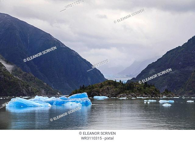Blue icebergs and face of Sawyer Glacier, mountain backdrop, Stikine Icefield, Tracy Arm Fjord, Alaska, United States of America, North America
