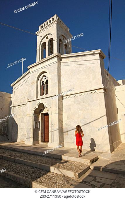 Tourist woman in feont of the Catholic church in the old town Chora, Naxos, Cyclades Islands, Greek Islands, Greece, Europe