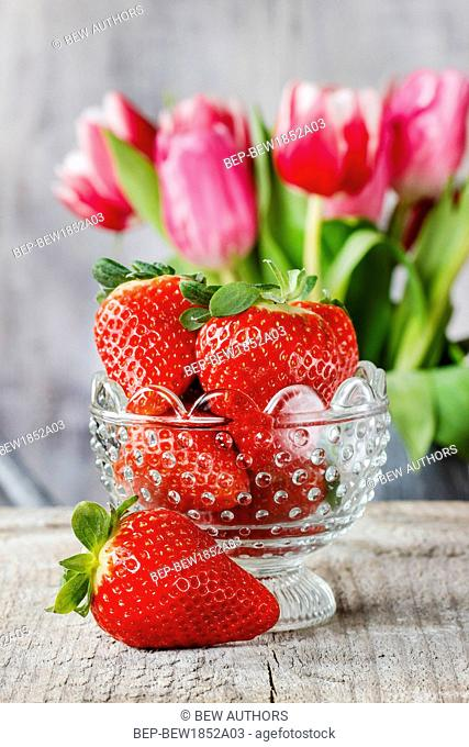 Goblet of fresh strawberries and bouquet of pink tulips in the background