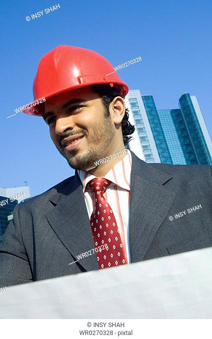 Young man wearing a red hard hat outdoors with skyscrapers in the background
