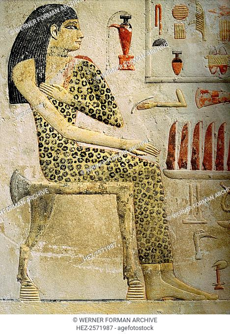 A slab-stela which belonged to Princess Nefertiabt. The princess is dressed as a priestess in a black-spotted panther skin and she is seated before an offering...