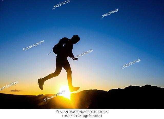Female hiker jogging on mountain ridge at sunrise on Gran Canaria, Canary Islands, Spain,