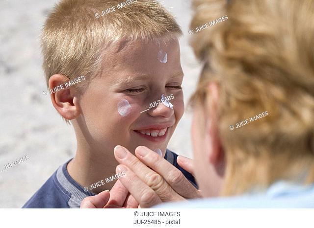 Grandmother applying sunscreen to grandsonÆs face