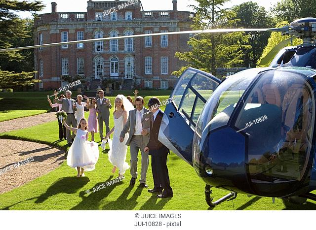 Wedding guests waving at bride and groom by helicopter