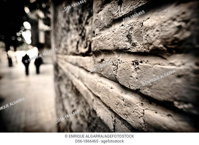 couple walking on the street near a brick wall. Valencia, Spain