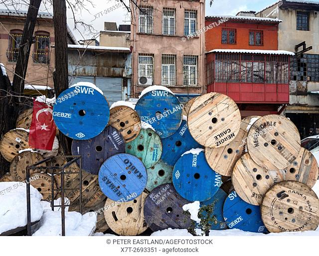 Old cable reels stacked in front of old houses on Karakoy waterfront, Istanbul, Turkey