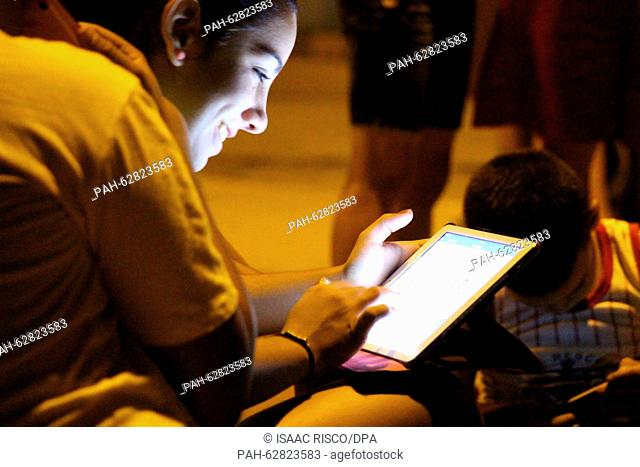 A young woman sits with a tablet computer on a square with public w-lan internet access in the Marianao district of Havana, Cuba, 16 October 2015