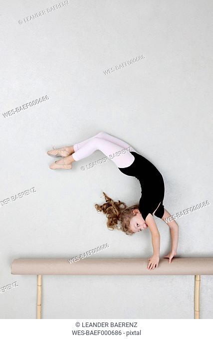 Girl exercising on balance beam