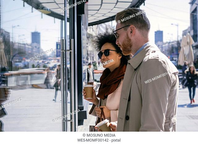 Couple in the city with takeaway coffee looking in shop window