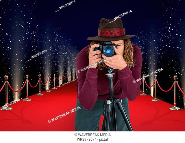 photographer with hat taking a photo with tripod in the red carpet . Lights behimd