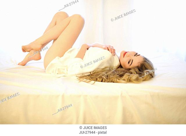 A woman with long blonde hair lying on a bed, knees drawn up