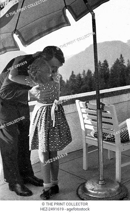 A little girl visits the Führer at Obersalzberg, Bavaria, Germany, 1936. Nazi leader Adolf Hitler (1889-1945) embraces a girl at his mountain retreat above...