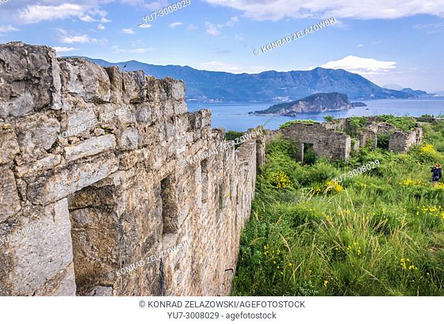 Ruins of 19th century Austrian Mogren Fortress in Budva city on the Adriatic Sea coast in Montenegro. Sveti Nikola Island on background
