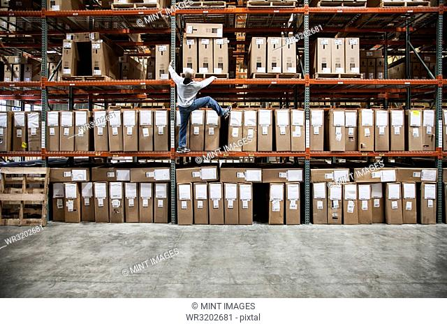 A warehouse worker trying to climb a rack of products in a distribution warehouse