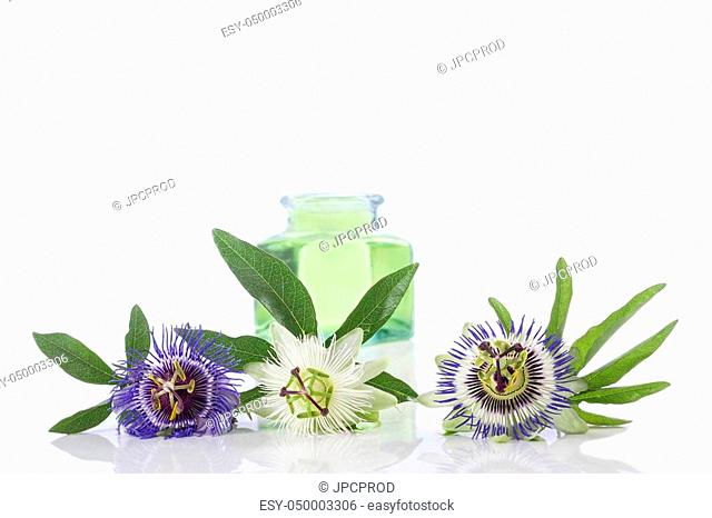 Passion flower with aromatherapy essential oil blue glass bottler isolated over white background