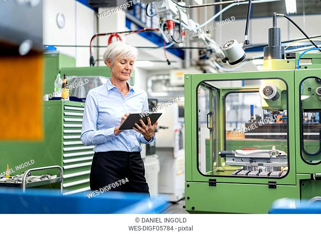 Senior businesswoman using tablet in a factory